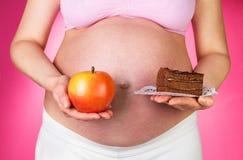 Mujer embarazada que sostiene la torta y la manzana del pedazo en fondo rosado Imagen de archivo libre de regalías