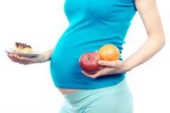 Mujer embarazada que sostiene las frutas y el pastel de queso, opción entre la nutrición sana y malsana durante embarazo Fotografía de archivo