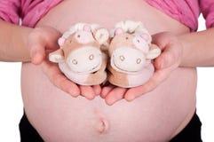 Mujer embarazada que sostiene los zapatos de bebé Fotografía de archivo libre de regalías