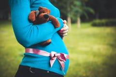 Mujer embarazada que sostiene un oso de peluche Fotografía de archivo libre de regalías