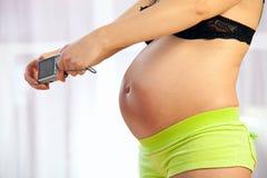 Mujer embarazada que toma el cuadro de su vientre Fotos de archivo