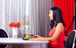 Mujer embarazada que trabaja en el cuaderno en casa Imagen de archivo