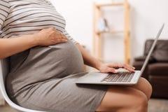 Mujer embarazada que trabaja en el ordenador portátil Foto de archivo libre de regalías