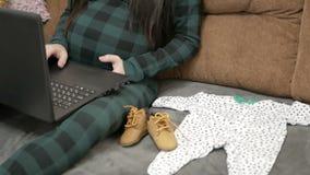 Mujer embarazada que trabaja en el ordenador portátil en casa almacen de video