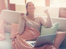 Mujer embarazada que trabaja en un sofá imagenes de archivo