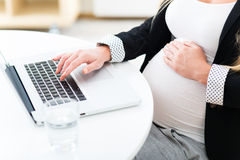 Mujer embarazada que usa la computadora portátil Imagenes de archivo