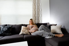 Mujer embarazada sana que miente en un sofá Fotografía de archivo libre de regalías