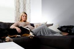Mujer embarazada sana que miente en un sofá con su perro Imagen de archivo