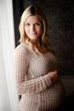 Mujer embarazada sana que se coloca en la ventana Foto de archivo libre de regalías