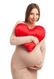 Mujer embarazada sonriente con la almohada en forma de corazón Imagen de archivo libre de regalías