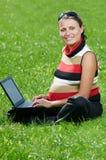 Mujer embarazada sonriente con la computadora portátil Fotos de archivo libres de regalías