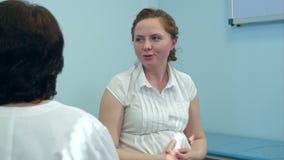 Mujer embarazada sonriente con su doctor en sitio de hospital almacen de metraje de vídeo