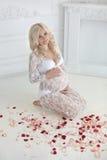 Mujer embarazada sonriente hermosa que se sienta en piso con la rosa del rojo Foto de archivo