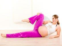 Mujer embarazada sonriente que hace ejercicio de los aeróbicos Imágenes de archivo libres de regalías