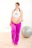 Mujer embarazada sonriente que hace ejercicios de la aptitud Foto de archivo libre de regalías
