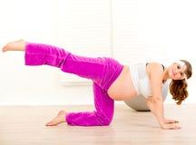 Mujer embarazada sonriente que hace ejercicios de la aptitud Imágenes de archivo libres de regalías