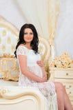 Mujer embarazada sonriente que se sienta en cama y el abrazo de la panza Fotos de archivo libres de regalías