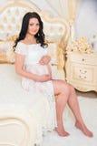 Mujer embarazada sonriente que se sienta en cama y el abrazo de la panza Fotos de archivo