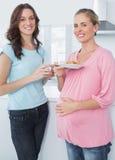 Mujer embarazada sonriente y su amigo Imagen de archivo