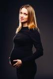 Mujer embarazada suave y sensual hermosa en el vestido negro que se opone a un fondo de la pared gris en el estudio Foto de archivo libre de regalías