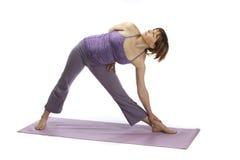 Mujer embarazada temprana que hace yoga y estirar Imagenes de archivo