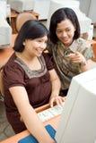 Mujer embarazada y amigo que aprenden el ordenador Foto de archivo