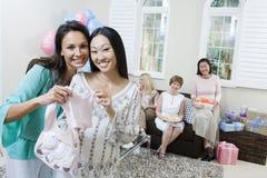 Mujer embarazada y amigo que sostienen la ropa del bebé fotografía de archivo libre de regalías