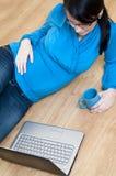 Mujer embarazada y computadora portátil Fotografía de archivo libre de regalías