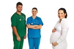 Mujer embarazada y doctores felices Imagenes de archivo