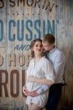 Mujer embarazada y hombre que presentan junto en el estudio Fotos de archivo