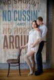 Mujer embarazada y hombre que presentan junto en el estudio imagenes de archivo
