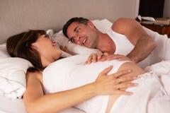 Mujer embarazada y marido en cama foto de archivo libre de regalías