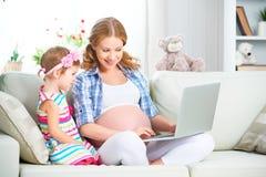 Mujer embarazada y niño de la familia feliz con un ordenador portátil en casa Imágenes de archivo libres de regalías