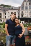 Mujer embarazada y su abrazo husbant y sonrisa La mujer puso su mano de su vientre Seis meses del embarazo fotos de archivo