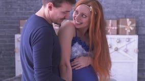 Mujer embarazada y su besarse del marido El vientre de la caricia del hombre de la esposa, señora está sonriendo metrajes