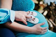 Mujer embarazada y su marido que llevan a cabo las manos en la panza con las muchachas Imagen de archivo libre de regalías