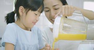 Mujer embarazada y su smoothie de colada de las frutas de la hija en vidrio de la licuadora almacen de metraje de vídeo