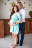 Mujer embarazada y su vientre conmovedor del marido con las manos Fotos de archivo libres de regalías