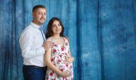 Mujer embarazada y su vientre conmovedor del marido con las manos Fotografía de archivo