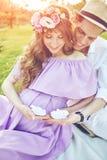 Mujer embarazada y sus paseos del marido en parque en la tarde Imagen de archivo libre de regalías
