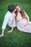 Mujer embarazada y sus paseos del marido en parque en la tarde Imagen de archivo
