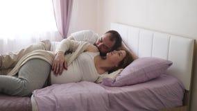 Mujer embarazada y un hombre en la mentira blanca de las camisetas metrajes