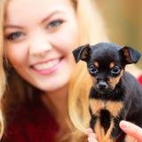 Mujer embrancing su perro de perrito Foto de archivo libre de regalías