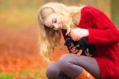 Mujer embrancing su perro de perrito Imagenes de archivo