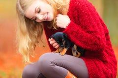 Mujer embrancing su perro de perrito Fotos de archivo
