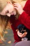 Mujer embrancing su perro de perrito Imagen de archivo libre de regalías