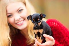 Mujer embrancing su perro de perrito Imagen de archivo