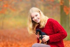 Mujer embrancing su perro de perrito Foto de archivo