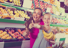Mujer emocionada con la hija en mercado de la fruta Imagenes de archivo