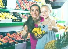 Mujer emocionada con la hija en mercado de la fruta Fotografía de archivo libre de regalías